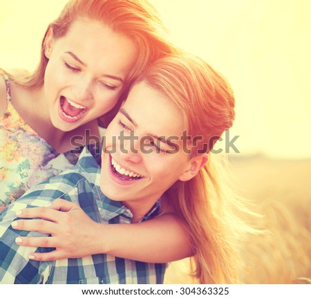 Beauty Couple having fun outdoors, relaxing on wheat field together. Happy girlfriend and boyfriend hugging, love concept. Beautiful Boy and Girl in love together - stock photo