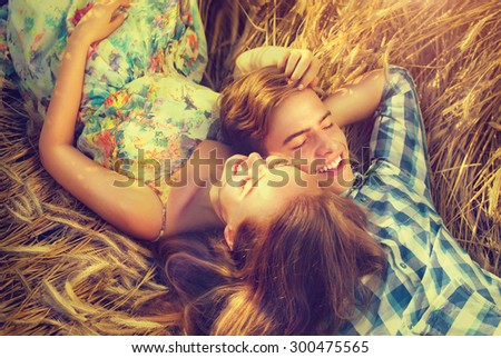 Beauty Couple Lying and relaxing on wheat field together. Teenage girlfriend and boyfriend having fun outdoors, kissing and hugging, first love concept. Teenagers Boy and Girl in love together - stock photo