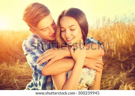 Beauty Couple relaxing on wheat field together. Happy girlfriend and boyfriend having fun outdoors, kissing and hugging, love concept. Beautiful Boy and Girl in love together - stock photo