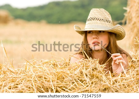 Beauty cowgirl relaxing in the straw in field - stock photo