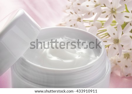 beauty cream and white flowers on pink fabric