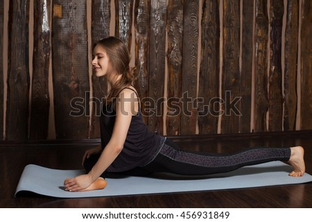 Beauty cute woman is training her legs with yoga exercises in yoga classes with wooden background. - stock photo