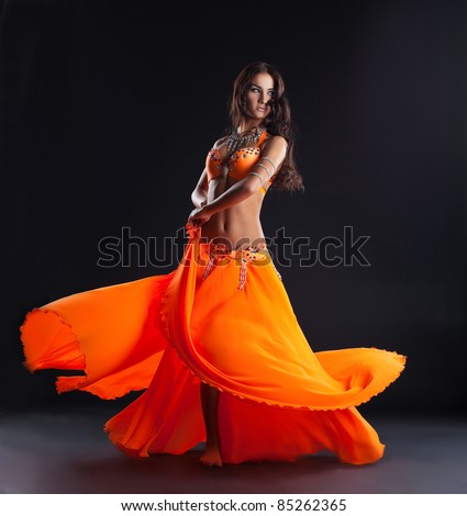 beauty dancer posing in traditional orange costume - stock photo