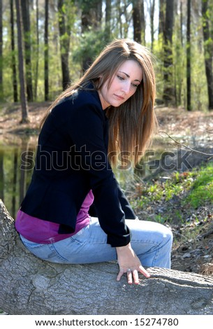 Beauty daydreams besides a quiet lake.  Sunlight filters through trees and highlights her hair.  Black jacket. - stock photo