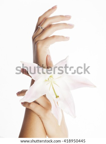 beauty delicate hands with manicure holding flower lily close up isolated on white perfect shape for spring - stock photo