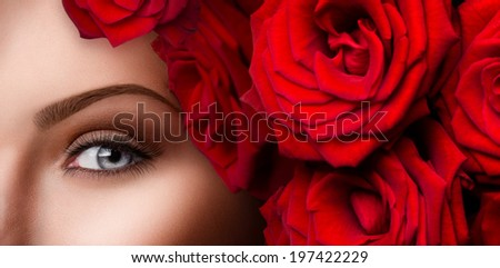 Beauty eyes makeup. Close-up of beautiful woman blue eye with red roses and stylish make up  - stock photo
