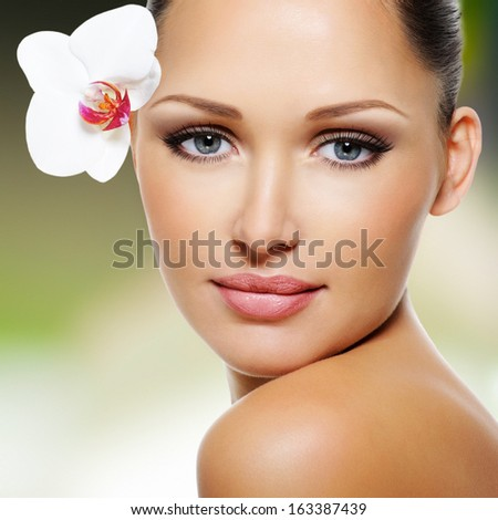 Beauty face of  beautiful woman with a white orchid flower. Skin care treatment. - stock photo
