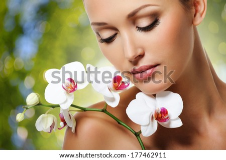 Beauty face of  beautiful woman with a white orchid flower. Skin care treatment. Green nature background - stock photo