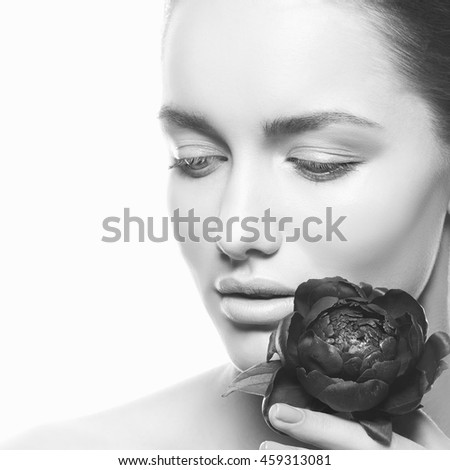 Beauty face of caucasian young brunette woman with peony flower in hand. Studio portrait. Isolated on white background. Black and white