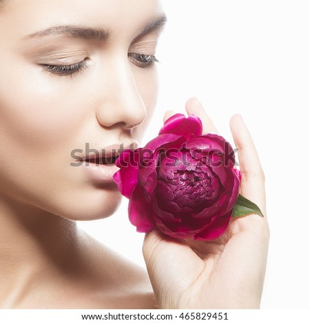 Beauty face of caucasian young brunette woman with peony flower in hand. Studio portrait. Isolated on white background.