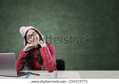 Beauty face of female student daydream, studying with laptop and books while wearing sweater and looking at bright lamp - stock photo