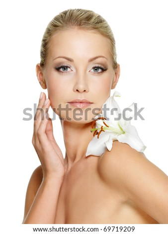 Beauty face of the young beautiful woman with flower. Female touching skin. Girl on white background - stock photo