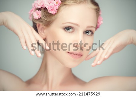 Beauty face of the young beautiful woman with pink flowers in her hair - stock photo