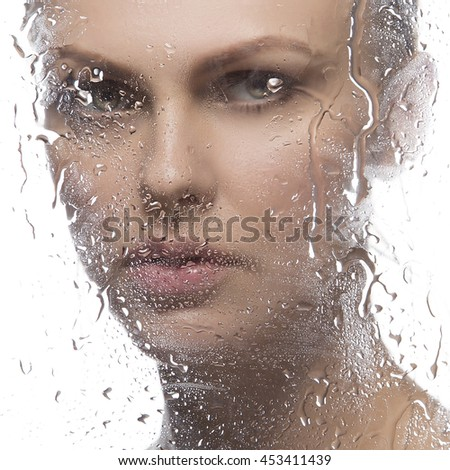 Beauty face of young caucasian woman near a mirror with water drops. Studio portrait. Isolated on white background.