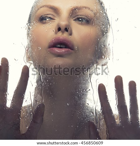 Beauty face of young caucasian woman near a mirror with water drops. Studio portrait. Isolated on white background. Toned