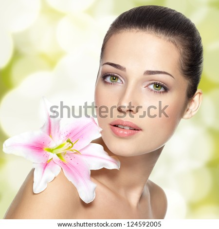 Beauty face of young woman with flower. Beauty treatment concept. Blinking Background. Bokeh - stock photo