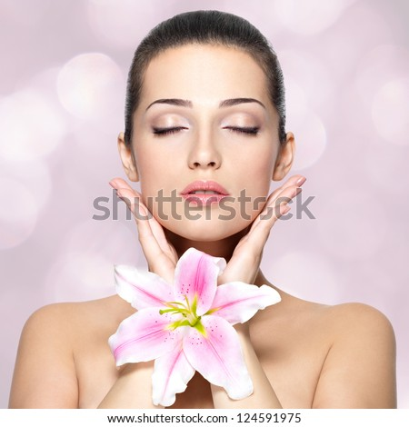 Beauty face of young woman with flower. Portrait of young woman with closed eyes. Blinking Background. Bokeh - stock photo
