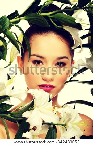 Beauty face of young woman with lily flowers.  - stock photo