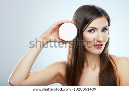 Beauty face portrait of young woman holding white container of skin care cream.