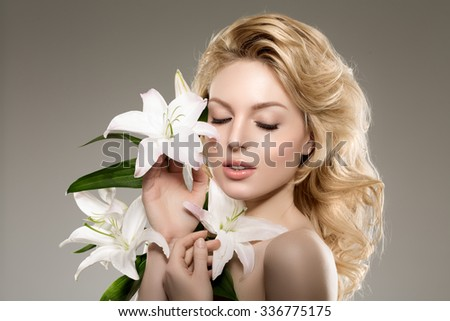 Beauty face woman, flowers, lily. Girl healthy model in spa salon. Cream treatment products. Facial skin terapy - stock photo