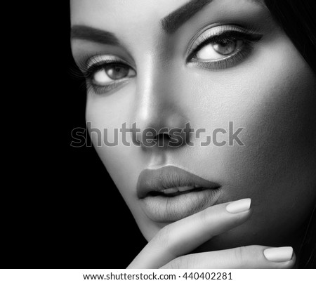 Beauty fashion black and white woman face portrait with perfect makeup and nails isolated on black