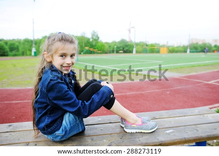 Beauty  fashion brunette school age kid girl in the blue jeans jacket and skirt watching soccer game on the school field - stock photo
