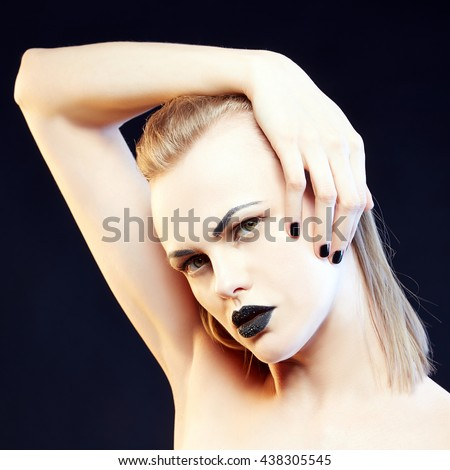 Beauty fashion caucasian model girl with black make up and dark lipstick. Isolated on black background.