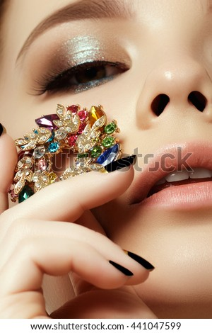 Beauty & fashion concept. Beautiful woman with jewelry, close-up. Beauty portrait of the fashion woman with evening make-up and black matte nails - stock photo