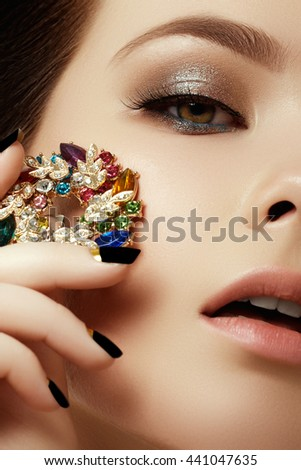 Beauty & fashion concept. Beautiful woman with jewelry, close-up. Beauty portrait of the fashion woman with evening make-up and black matte nails