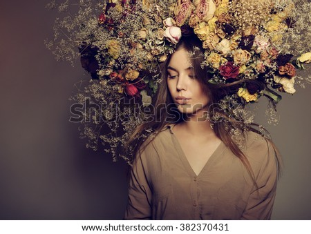 Beauty fashion female portrait with large garland dried flowers. Beautiful woman with wreath of roses  - stock photo