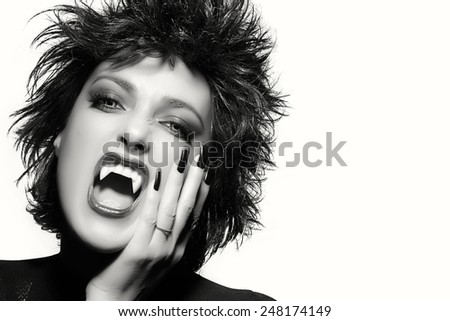 Beauty fashion female vampire with light colored evil eyes baring her fangs at the camera in a Halloween concept. Black and white portrait with copy space for text - stock photo