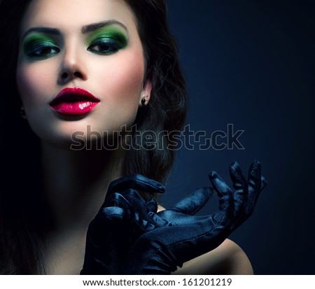 Beauty Fashion Glamour Girl Portrait. Vintage Style Model Girl Wearing Gloves. Holiday Glamour Make-up. Red Lipstick and Deep Green Eyeshadows. Darkness. Beautiful Mysterious Woman Dark Portrait