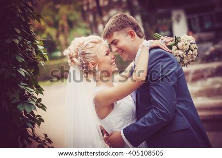 Beauty / Fashion / Hairstyle / Makeup photo shoot /  Wedding.  Wedding couple with bouquet outdoors. emotional portrait.  insyagram toning effect - stock photo