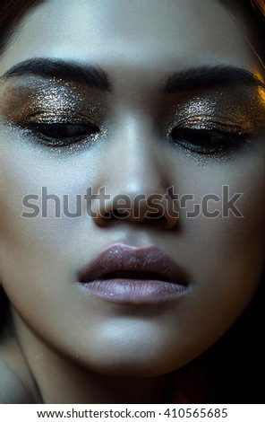 Beauty, fashion, make up. Close up portrait of woman in golden glitters in blue light