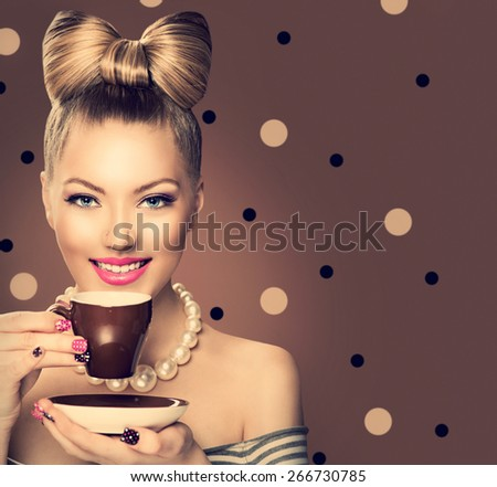 Beauty fashion model girl drinking coffee or tea. Beautiful young woman with cup of hot beverage. Retro styled vintage lady with professional make up, funny bow hair style. Polka dots brown background - stock photo