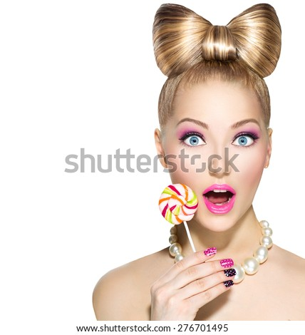 Beauty fashion model girl Eating colourful lollipop. Lollypop. Surprised Young funny woman with bow hairstyle, pink nail art and makeup isolated on white background - stock photo
