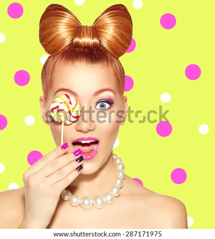 Beauty fashion model girl Eating colourful lollipop. Surprised Young funny woman with bow hairstyle, pink nail art and makeup over bright green with pink polka dots background - stock photo