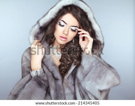 Beauty Fashion Model Girl in Fur Coat, Beautiful brunette woman with wavy hair and makeup. - stock photo