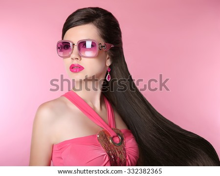 Beauty fashion model girl in sunglasses with bright makeup, long hair, luxury earrings jewelry. Glamour woman isolated on pink studio background.