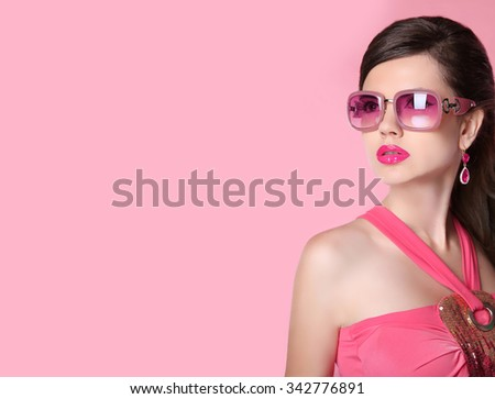 Beauty fashion model girl in sunglasses with bright makeup, long hair, luxury earrings jewelry. Glamour woman isolated on pink studio background. - stock photo