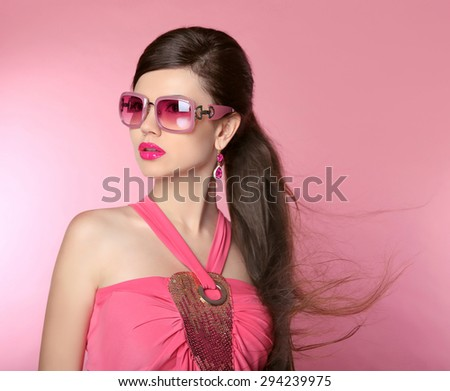Beauty fashion model girl in sunglasses with bright makeup, long hair, manicured nails. Glamour woman isolated on pink studio background.