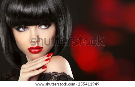 Beauty Fashion model girl portrait. Makeup and red manicured nails. Bob black hairstyle. Brunette woman posing over black background.