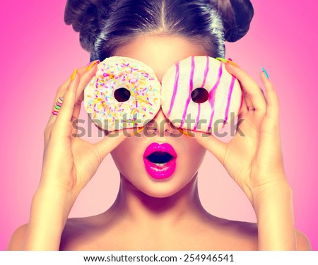 Beauty fashion model girl taking sweets and colorful donuts. Funny joyful Vogue styled woman with sweets on pink background. Diet, dieting concept. Junk food, Slimming, weight loss - stock photo