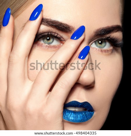 Beauty Fashion Model Girl with Blue Make up, Long Lushes. Fashion Trendy Caviar Blue Manicure. Nail Art. bright Lipstick and Nail Polish. Isolated over black background