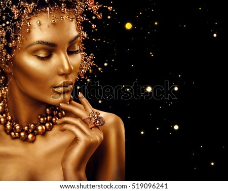 Beauty Fashion model girl with Golden Makeup, Gold skin make up, hair and jewellery on black background. Gold earrings, ring and necklace. Metallic, glance Fashion art portrait, Hairstyle and make up