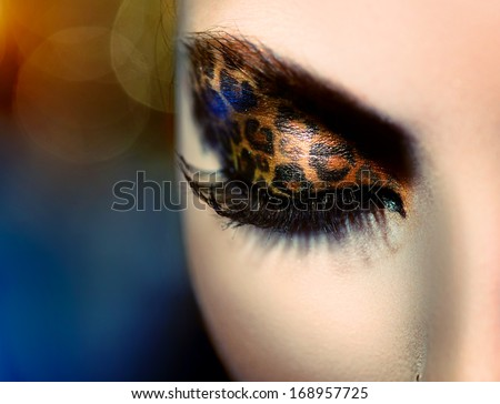 Beauty Fashion Model Girl with Holiday Leopard Makeup. Golden Wild Cat Eyes Make-up Eyeshadow. Beautiful Woman Face with Perfect skin. Animal Make up  - stock photo