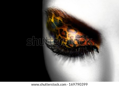 Beauty Fashion Model Girl with Holiday Leopard Makeup. Golden Wild Cat Eyes Make-up Eyeshadow. Beautiful Woman Face with Perfect skin. Animal Make up. Black and White Portrait closeup - stock photo