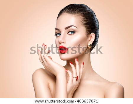 Beauty Fashion Model Woman face. Portrait with perfect skin. Red Lips and Nails. Beautiful Sexy Brunette Woman with Luxury Makeup and Manicure over beige background - stock photo