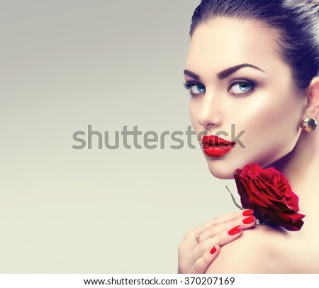 Beauty Fashion Model Woman face. Portrait with Red Rose flower. Red Lips and Nails. Beautiful Brunette Woman with Luxury Makeup and Manicure.  - stock photo