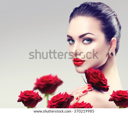 Beauty Fashion Model Woman face. Portrait with Red Rose flowers. Red Lips and Nails. Beautiful Brunette Woman with Luxury Makeup, perfect skin. Valentine - stock photo